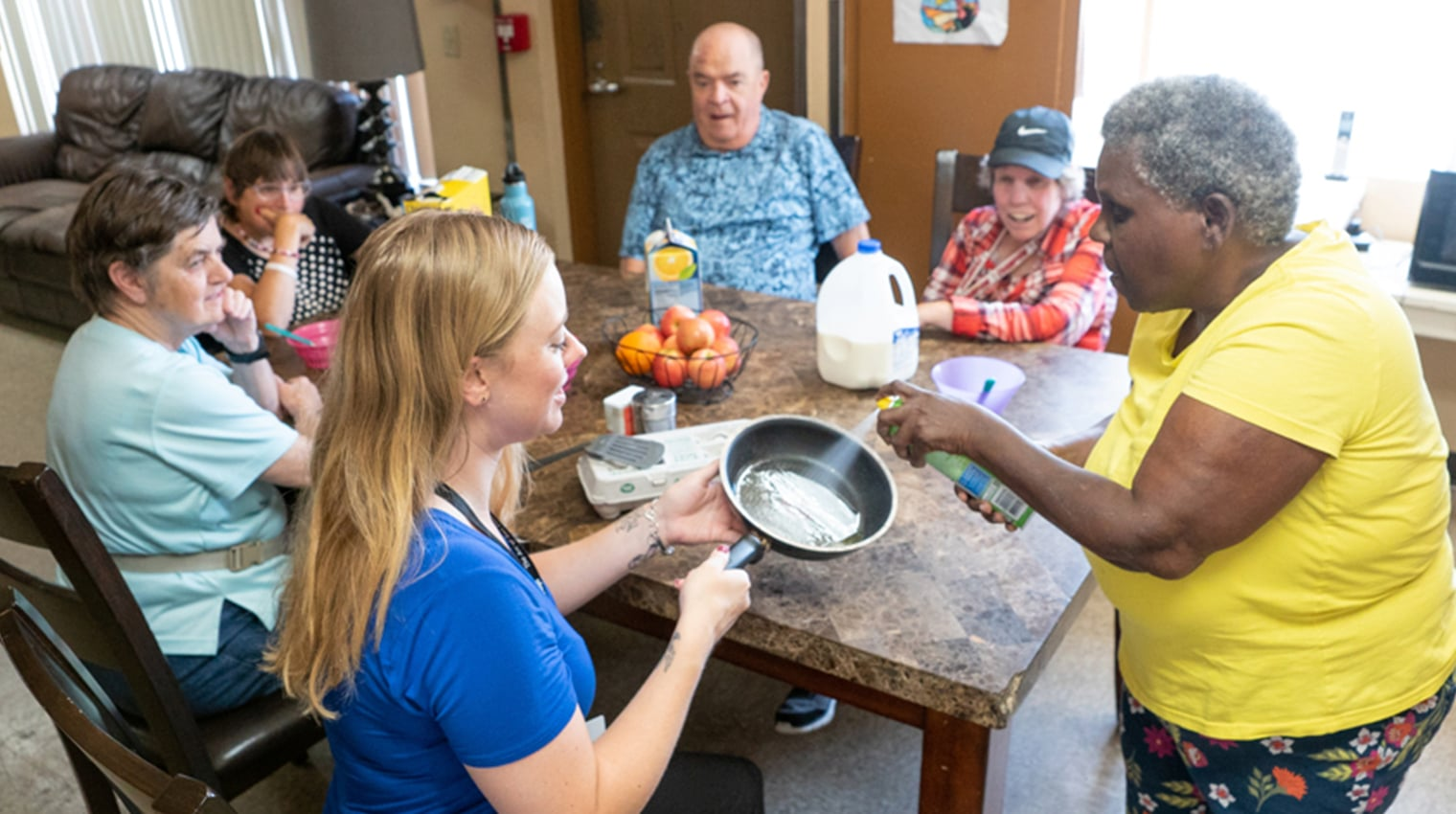 People in a community home preparing a meal together