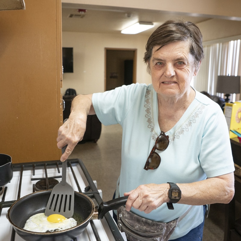 Woman frying an egg