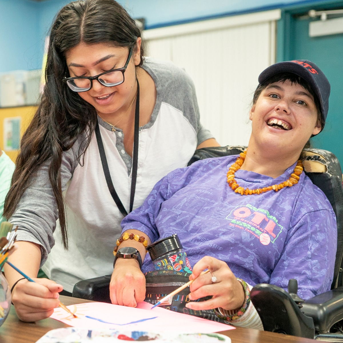 Woman assisting a disabled woman with an art project